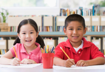 Kindergarten children sitting at desk and writing in classroom