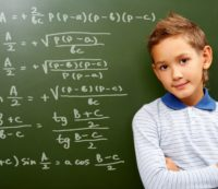 7844008 - portrait of smart schoolchild by the blackboard with sums on it looking at camera